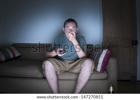 man covering mouth watching tv