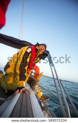 Man Cranking A Winch On Yacht In Sea #589072334