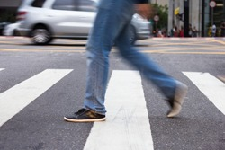 Man crossing pedestrian lane. Blurred by movement.