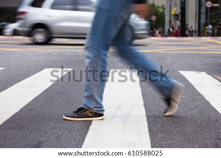 Man crossing pedestrian lane. Blurred by movement. #610588025
