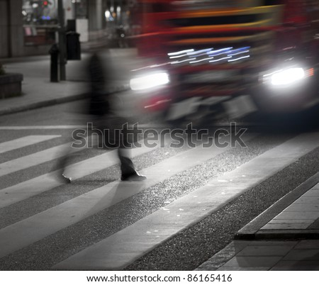Man crossing street in front of big vehicle