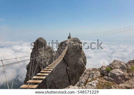 Man crossing the chasm on the hanging bridge (focus on the middle of bridge)