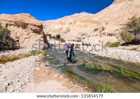 Man crossing the creek in  Wadi Hasa in Jordan