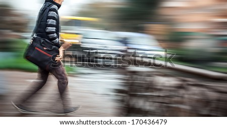 Man crossing the street at a crosswalk. Intentional motion blur