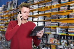 Man customer talking by phone near shelves with large collection of DVDs in store