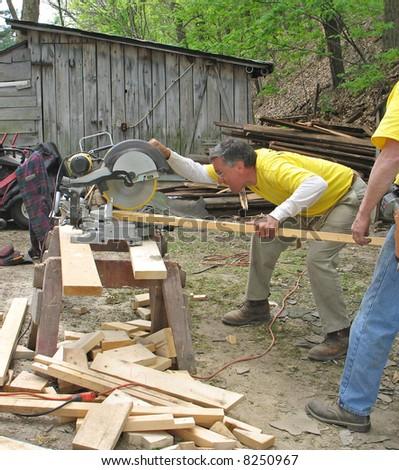 Man cuts lumber with chop saw