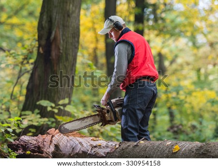 Man cutting a branch with chainsaw #330954158