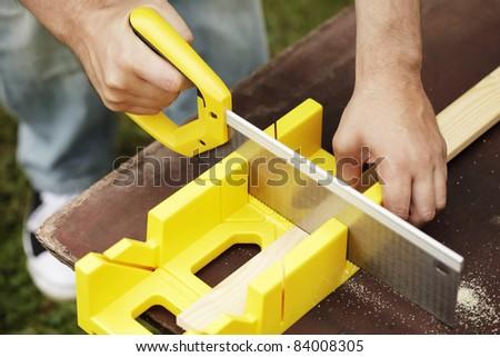 Man cutting a slat of wood using a saw and miter box.