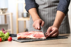 Man cutting fresh raw meat on wooden table in kitchen, closeup