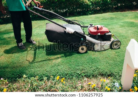 man cutting grass with lawn mower #1106257925