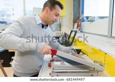 man cutting print with precision machine