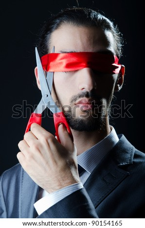 Man cutting ribbon on his eyes