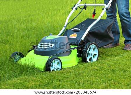Man cutting the grass with electric lawn mower  #203345674