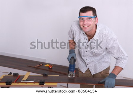 Man cutting tongue and groove floorboards with a jigsaw - stock photo