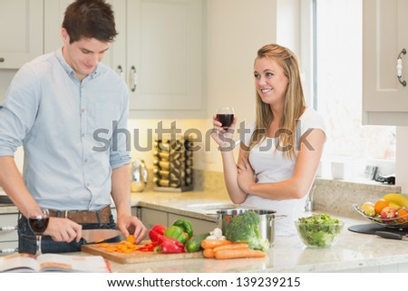 Man cutting vegetables with woman drinking wine in kitchen