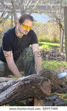 Man cutting wood with electric saw - stock photo