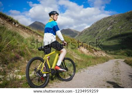 Man cycling down a dirt road #1234959259