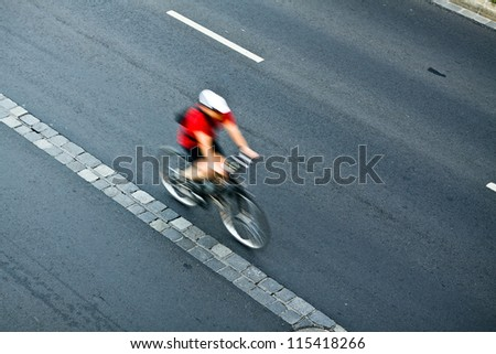 Man cycling on city street, motion blur, commuting cyclist