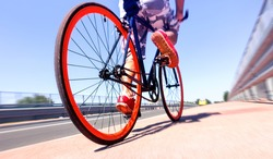 Man cycling on sport bike - Bicycle wheels and road perspective with cyclist riding  blue summer sky background - Concept of alternative transportation  environmental friendly  with radial zoom filter