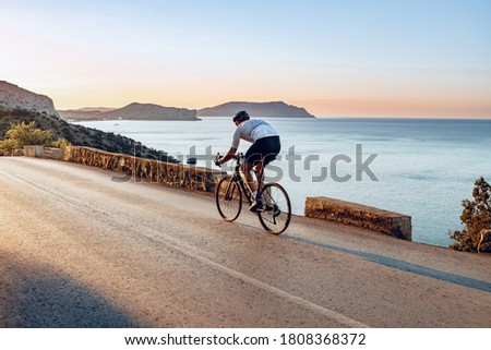 Man cyclist pedaling on a road bike outdoors in sun set Foto d'archivio ©