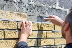 Man decorates the facade of the fence with decorative torn bricks, close up view. Work at home during quarantine, DIY