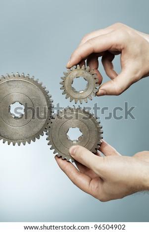 Man designing a mechanical system using old cog gear wheels.
