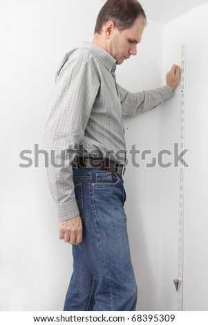 Man determining the vertical directions using plumb bob while-out assembling the closet