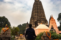 man devotee meditating for almighty god with temple background image is taken at mahabodhi temple bodhgaya bihar india. it is the place where buddha got enlightened.
