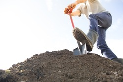 man digging the ground with shovel
