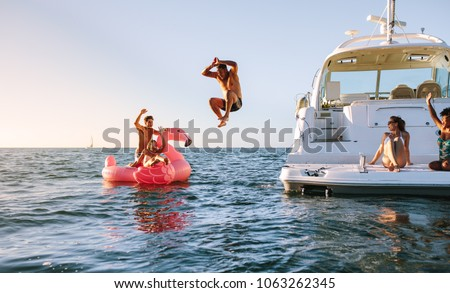 Photo of  Man diving in the sea with friends sitting on yacht and inflatable toy. Group of friends enjoying a summer day on a inflatable toy and yacht.