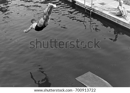 man diving into swimming pool