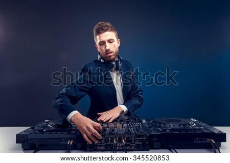 Man DJ in dark suit play music on a Dj\'s mixer. Studio shot. Dark blue background