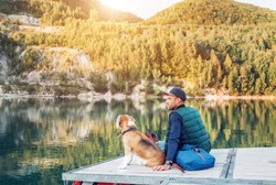 Man dog owner and his friend beagle dog are sitting on the wooden pier on the mountain lake and enjoying the landscape during their walking in the autumn season time. Human and pet concept image.