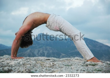 Man doing a bridge on rock