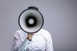 Man Doing Announcement Using Megaphone Against Gray Background
