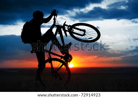 Man doing bicycle juggle on sunset background - stock photo