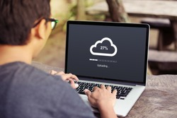 Man doing cloud uploading on laptop / computer at the park / outdoor