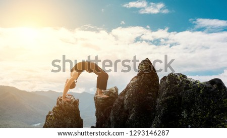 man doing complex Yoga exercise headstand. Amazing Yoga landscape in beautiful mountains. Dangerous stunts traceur standing on his hands on the edge of a cliff.