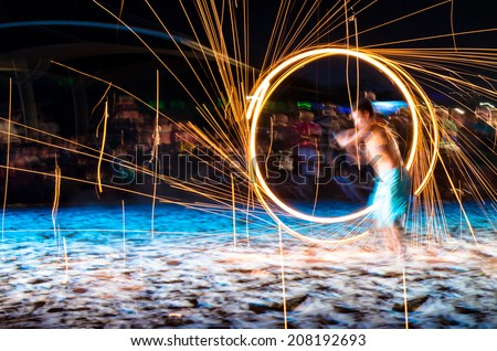 man doing fire show on beach at night