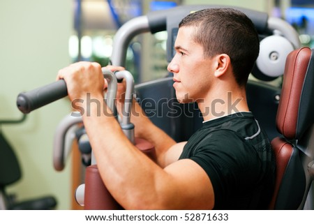 Man doing fitness training on a butterfly machine with weights in a gym - stock photo
