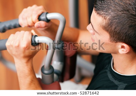 Man doing fitness training on a butterfly machine with weights in a gym