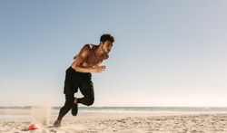 Man doing fitness workout at a beach on a sunny day. Athletic man setting off for a sprint on the beach.