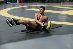 Man doing fitness workout, practicing abs exercise with med ball at street. Male athlete exercising, doing russian twist with medicine ball outdoors