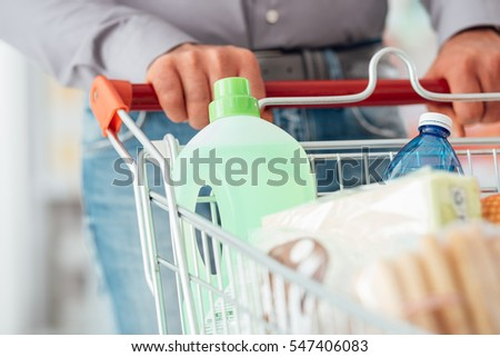 Man doing grocery shopping at the supermarket, he is pushing a full trolley, hands detail close up
