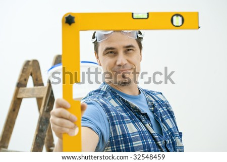 Man doing home improvement, using square level tool. Isolated on white background.