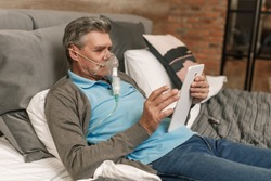 Man doing inhalation through oxygen mask at home bedroom and use laptop.