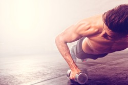 Man doing push-up exercise with dumbbell