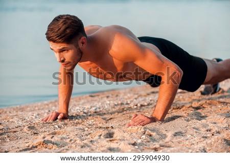 Man doing push-ups. Handsome young muscular man doing push-ups at the riverbank
