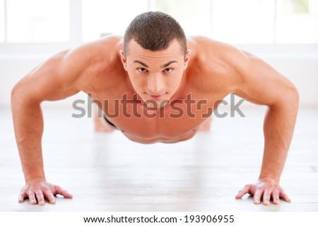 Man doing push-ups. Young muscular man doing push-ups and looking at camera