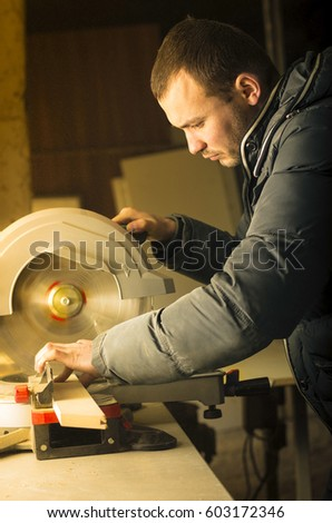 Man doing some carpentry work in a workshop.